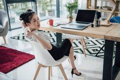 Empresaria asiática joven que se sienta en la tabla con el ordenador portátil y que mira lejos foto de archivo libre de regalías