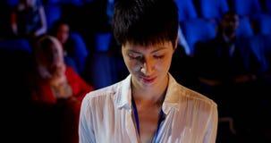 Empresaria asiática joven que usa la tableta digital durante seminario del negocio en el auditorio 4k almacen de metraje de vídeo