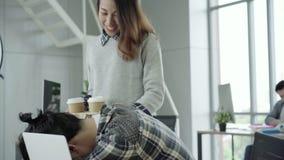Empresaria asiática que da el café a su colega que está trabajando con el ordenador portátil en la oficina almacen de video