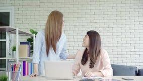 Empresaria asiática que da el café a su colega que está trabajando con el ordenador portátil en la oficina