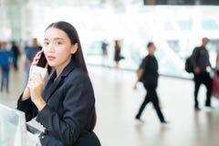 Empresaria asiática que habla el teléfono móvil y que sostiene una taza de café imágenes de archivo libres de regalías