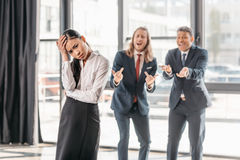 Empresaria asiática que se coloca en oficina, hombres de negocios detrás de gesticular y la risa imagen de archivo