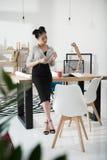Empresaria asiática que se inclina en la tabla de la oficina y que sostiene el lápiz Imagen de archivo libre de regalías