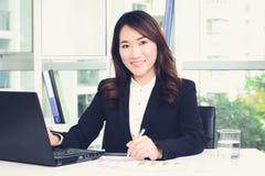 Empresaria asiática que trabaja en la oficina Foto de archivo