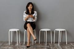 empresaria asiática sonriente con esperar del smartphone fotografía de archivo