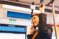 Empresaria asiática sonriente feliz que habla en el teléfono que conmuta imagenes de archivo