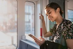 Empresaria asiática sonriente que monta en un tren usando su teléfono móvil imagen de archivo