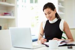 Empresaria asiática Working From Home en el ordenador portátil Imagen de archivo