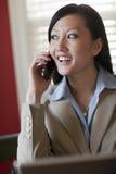 Empresaria asiática joven en su teléfono Imagenes de archivo