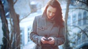 Empresaria atractiva al aire libre con el teléfono móvil metrajes