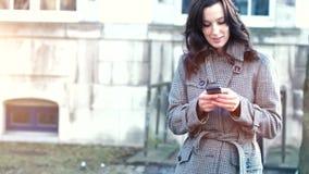 Empresaria atractiva al aire libre con el teléfono móvil almacen de video