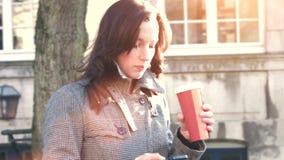 Empresaria atractiva al aire libre con el teléfono móvil y el café almacen de video