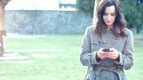 Empresaria atractiva al aire libre con el teléfono móvil y el café almacen de metraje de vídeo