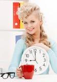Empresaria atractiva con el reloj y la taza roja Foto de archivo libre de regalías
