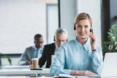 empresaria atractiva en auriculares usando el ordenador portátil y la sonrisa fotografía de archivo libre de regalías