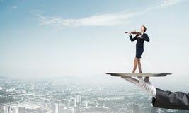 Empresaria atractiva en la bandeja del metal que juega el fondo del paisaje urbano del aginst del violín Imagen de archivo