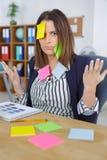 Empresaria atractiva en la oficina con el post-it en la frente Imagen de archivo