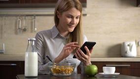 Empresaria atractiva joven hermosa que come copos de maíz para el desayuno y que usa su smartphone metrajes