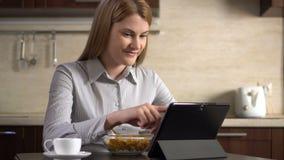 Empresaria atractiva joven hermosa que come copos de maíz para el desayuno y que usa su tableta metrajes