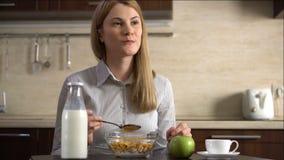 Empresaria atractiva joven hermosa que come los copos de maíz para el desayuno en cocina Taza de café almacen de video