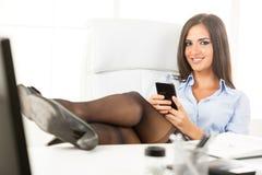 Empresaria atractiva With Legs On el escritorio imagenes de archivo