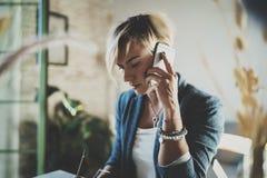 Empresaria atractiva que habla con el socio vía el teléfono moderno mientras que escribe una cierta información en cuaderno mient Fotografía de archivo libre de regalías