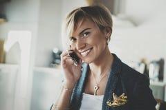 Empresaria atractiva que habla con el socio vía el teléfono moderno mientras que escribe una cierta información en cuaderno mient Fotografía de archivo