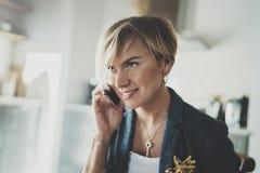 Empresaria atractiva que habla con el socio vía el teléfono moderno mientras que escribe una cierta información en cuaderno mient Foto de archivo