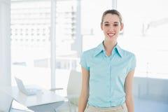 Empresaria atractiva que lleva la blusa azul que presenta en su oficina Fotografía de archivo libre de regalías