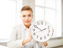 Empresaria atractiva que muestra el reloj blanco imagen de archivo