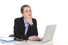 Empresaria atractiva que piensa y que parece loca mientras que trabaja en el ordenador Foto de archivo libre de regalías