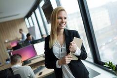 Empresaria atractiva que usa la tableta digital en oficina foto de archivo