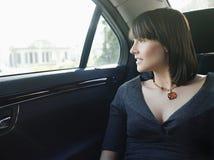 Empresaria At Back Seat del coche que mira hacia fuera la ventana Foto de archivo libre de regalías