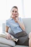 Empresaria bastante con clase que llama por teléfono mientras que se sienta en el sofá Fotografía de archivo