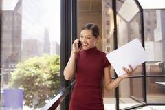 Empresaria blanca joven en el teléfono que mira hacia fuera la ventana de la oficina Imagenes de archivo
