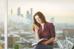Empresaria bonita con smartphone y el libro Imagenes de archivo