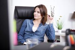 Empresaria bonita en el dril de algodón que se sienta en silla Imagen de archivo