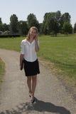 Empresaria bonita en el parque; en el teléfono imagen de archivo