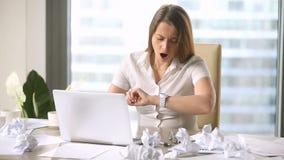 Empresaria bonita joven que bosteza, comprobando el tiempo, trabajando extraordinariamente después de horas almacen de video