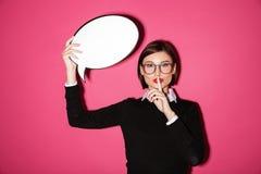 Empresaria bonita que lleva a cabo la burbuja del discurso y que muestra la burbuja del discurso fotos de archivo