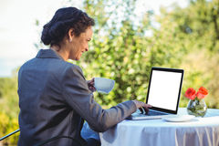 Empresaria bonita que usa el ordenador portátil y comiendo café Fotos de archivo