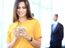 Empresaria bonita que usa el teléfono elegante imagen de archivo