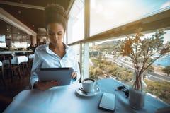 Empresaria brasileña seria en café con PC de la tableta durante el Br Foto de archivo