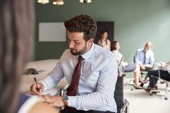 Empresaria And Businessman Collaborating en tarea junto en el día graduado de la evaluación del reclutamiento fotografía de archivo