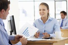 Empresaria And Businessman Working en el escritorio junto Fotos de archivo libres de regalías