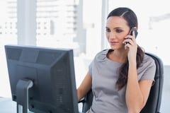 Empresaria cabelluda oscura pacífica que tiene una conversación telefónica Imágenes de archivo libres de regalías