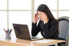 Empresaria cansada de Asia con dolor de cabeza en la oficina Foto de archivo