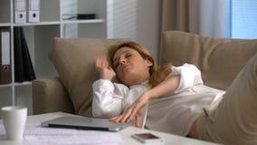 Empresaria cansada que duerme en el sofá en la oficina con el ordenador portátil en su revestimiento almacen de metraje de vídeo