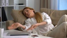 Empresaria cansada que duerme en el sofá en la oficina con el ordenador portátil en su revestimiento almacen de video