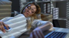 Empresaria cansada que duerme en el sofá en la oficina con el ordenador portátil y el teléfono metrajes